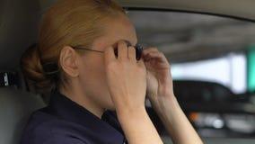 O oficial de patrulha fêmea que põe sobre óculos de sol no automóvel do pelotão, apronta-se para a ação vídeos de arquivo
