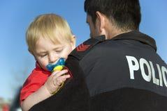 O oficial de polícia prende o bebê Fotografia de Stock