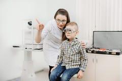 O oftalmologista do doutor da recepção da criança seleciona vidros da lente, vista do olho da verificação fotos de stock royalty free