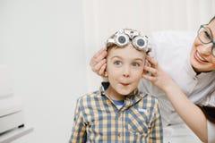 O oftalmologista do doutor da recepção da criança seleciona vidros da lente, vista do olho da verificação imagens de stock royalty free