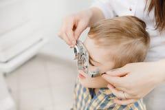 O oftalmologista pediatra do doutor verifica a visão do menino da criança Seleção do conceito de lentes dos vidros fotografia de stock royalty free