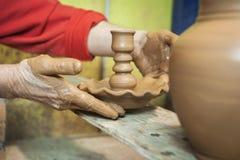 O oleiro colocando em uma tabela da madeira possui o castiçal do freshl Fotos de Stock
