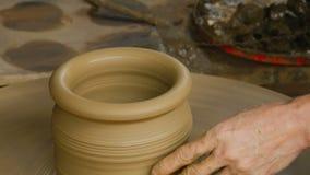 O oleiro dá forma ao potenciômetro de argila com mãos video estoque