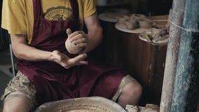 O oleiro dá forma ao produto da argila com as ferramentas da cerâmica na roda do ` s do oleiro, vista superior, cinemático tonifi video estoque