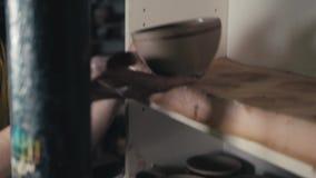 O oleiro dá forma ao produto da argila com as ferramentas da cerâmica na roda do ` s do oleiro, vista superior, cinemático tonifi vídeos de arquivo