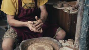 O oleiro dá forma ao produto da argila com as ferramentas da cerâmica na roda do ` s do oleiro, vista superior, cinemático tonifi filme