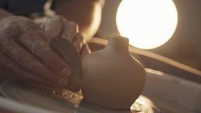 O oleiro dá forma ao produto da argila com ferramentas da cerâmica filme