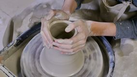 O oleiro d? forma ao produto da argila na roda de oleiro video estoque