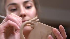 O oleiro da menina faz toques finais ao copo cru da argila usando a borla video estoque