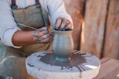 O oleiro está criando o produto de cerâmica na roda do ` s do oleiro fotografia de stock