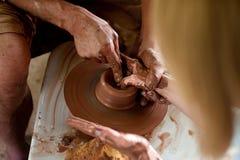 O oleiro está moldando da argila em uma roda do ` s do oleiro As mãos do oleiro Fotos de Stock