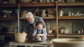 O oleiro experimentado avô de inquietação é ensinando a rapaz pequeno como trabalhar com argila na roda do ` s do oleiro O neto e vídeos de arquivo