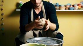 O oleiro masculino considerável amassa a argila antes do trabalho na oficina da cerâmica vídeos de arquivo