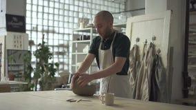 O oleiro novo está amassando a argila na tabela na oficina da cerâmica vídeos de arquivo