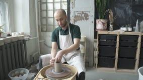O oleiro novo está fazendo o potenciômetro de argila na máquina de giro na oficina da cerâmica video estoque