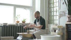 O oleiro novo está terminando o trabalho ao sentar-se na oficina da cerâmica vídeos de arquivo