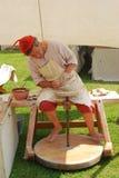 O oleiro vestido no traje medieval faz um vaso Foto de Stock