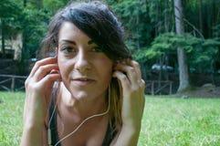 O olhar bonito da menina e escuta música no parque Foto de Stock Royalty Free