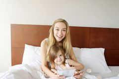 O olhar da mãe do retrato na câmera abraça a filha pequena na cama branca com cartão, tabuleta e luz do sol de crédito fotografia de stock royalty free