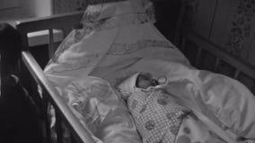 O olhar do rapaz pequeno in camera e come o pão no berço com o bebê no tecido, com chupeta Miúdos filme