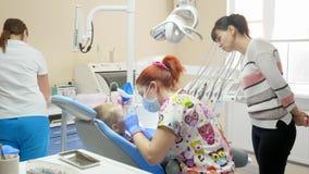 O olhar dos pais observa como o dentista trata os dentes ao paciente pequeno no escritório dental filme