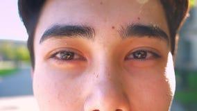 O olhar focalizado do close-up do homem asiático com marrom escuro agradável eyes, não se mover, exterior video estoque