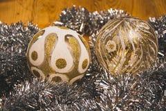 O olhar muito próximo e bonito nas duas bolas de vidro prata-douradas do Natal Imagens de Stock Royalty Free