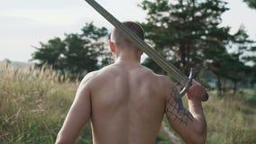 O olhar traseiro do lutador livre com espada anda em um estepe lentamente vídeos de arquivo