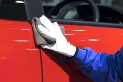 O operador branco da luva que guarda o pano está limpando o carro imagens de stock