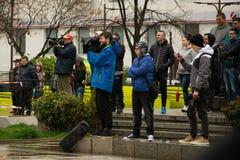O operador cinematográfico está filmando um evento na cidade - público no fundo fotografia de stock