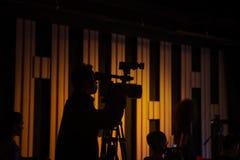 O operador cinematográfico está trabalhando no estúdio durante o tiro imagens de stock