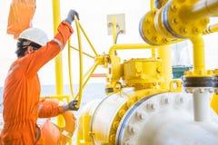 O operador da produção que abre a válvula de bola grande para permitir o gás corre através do encanamento na plataforma de petról imagens de stock royalty free