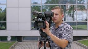 O operador da tevê remove o vídeo com uma câmara de vídeo profissional, que esteja em um tripé video estoque