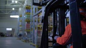 O operador inspeciona o armazém no caminhão de empilhadeira que conduz através das cremalheiras com mercadoria video estoque
