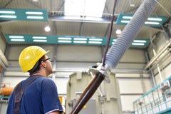 O operador instala um transformador em uma planta industrial em mechan imagem de stock