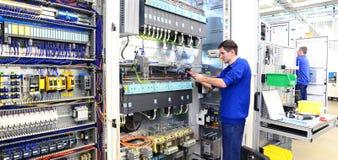O operador monta a máquina em uma fábrica - produção do interruptor c imagem de stock