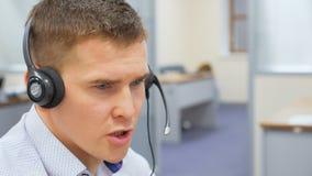 O operador novo com microfone dos auriculares trabalha no centro de serviço video estoque