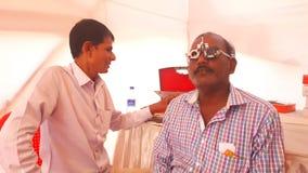 O optometrista verifica o teste da visão do olho de um ancião Imagem de Stock Royalty Free