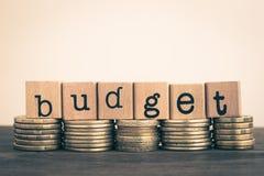 O orçamento na moeda, pilha da palavra das moedas de ouro imagem de stock