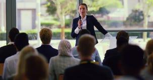 O orador fêmea fala em um seminário do negócio no escritório moderno 4k vídeos de arquivo