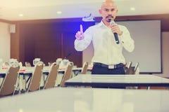 O orador guardou o microfone em sua mão e mostra seu dedo indicador ao ouvinte com sala de conferências e o projetor obscuros foto de stock royalty free