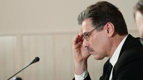 O orador incomodado atentamente escuta uma pergunta do journalista em uma conferência de imprensa e responde-lhe, vista lateral vídeos de arquivo