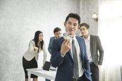 O orgulho feliz do homem de negócios com copo da vitória e o negócio team ciumento foto de stock royalty free