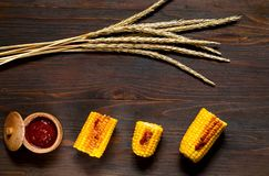 O original grelhou o milho com molho picante em um fundo de madeira Vista superior, espaço da cópia foto de stock