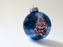 O ornamento azul brilhante do feriado reflete brilhantemente a árvore de Natal colorida do Lit Fotografia de Stock