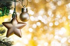 O ornamento do Natal decora na árvore de abeto com bokeh do ouro Imagem de Stock Royalty Free