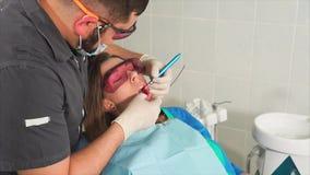 O orthodontist do doutor com vidros clarea os dentes de uma jovem mulher com um laser vídeos de arquivo