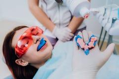O orthodontist do doutor executa um procedimento para limpar os dentes imagem de stock royalty free