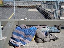 O os sem-abrigo dorme sob cobertores no meio-dia imagem de stock