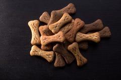 O osso deu forma a cookies ou a deleites do cão, no fundo de madeira escuro fotografia de stock royalty free